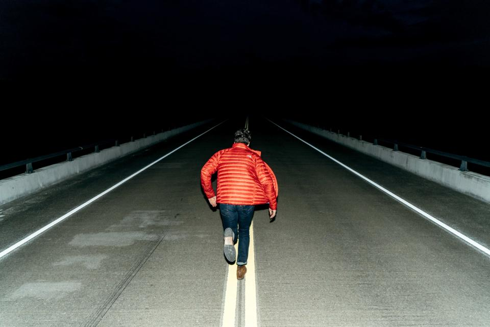 people man running orange jacket road street empty dark night