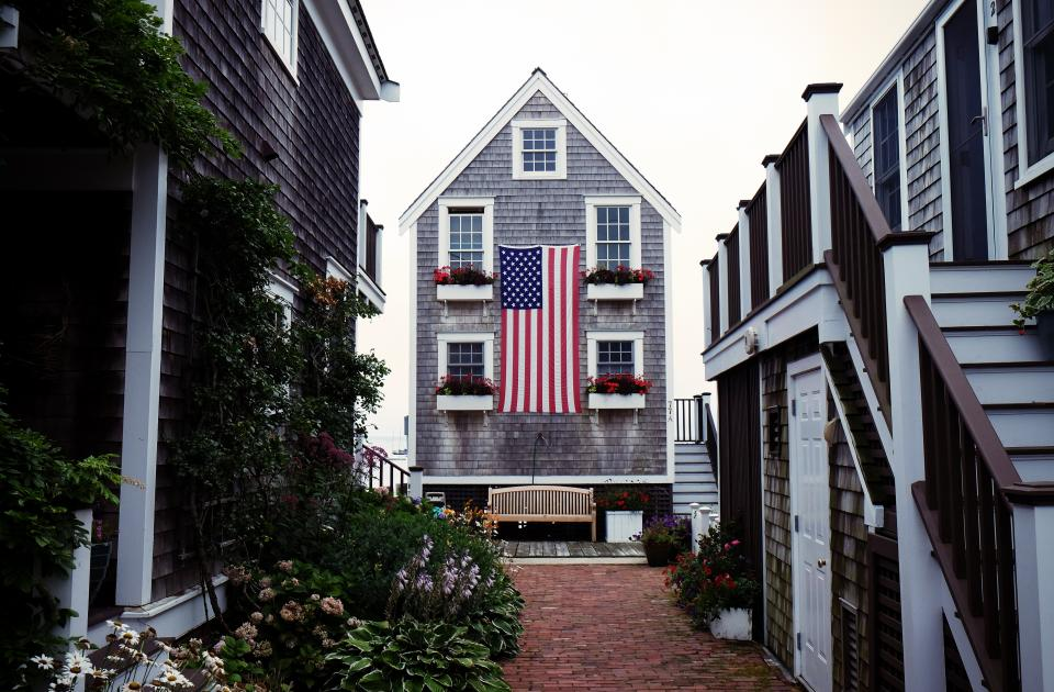 american flag usa united states house siding flowers pots cobblestone plants windows steps stairs railing door