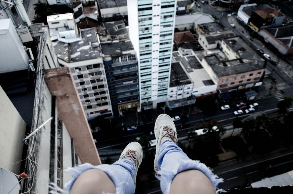 feet shoes knees buildings sitting view vehicle hotel road top ripped jeans city urban