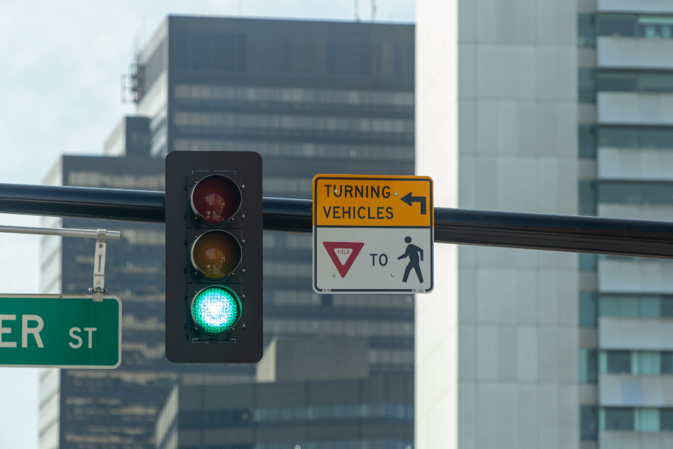city traffic light green street road building car signal driving downtown daytime urban buildings yield sign auto