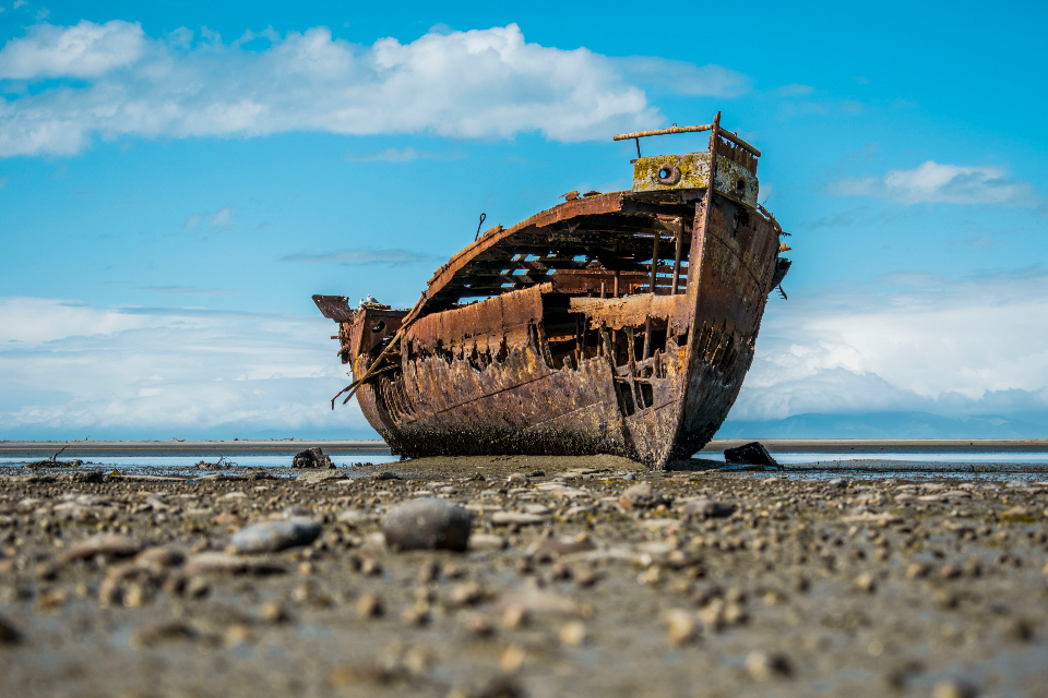 ship wreck rust boat abadoned weathered seashore aged sea ocean beach shore sand rocks sky clouds