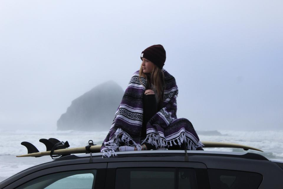 sea ocean water waves nature rock hill fog sky cold beach car vehicle people ride girl woman travel