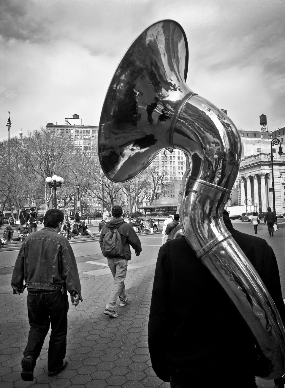 tuba horn instrument music band cobblestone pedestrians walking lamp posts buildlings backpack
