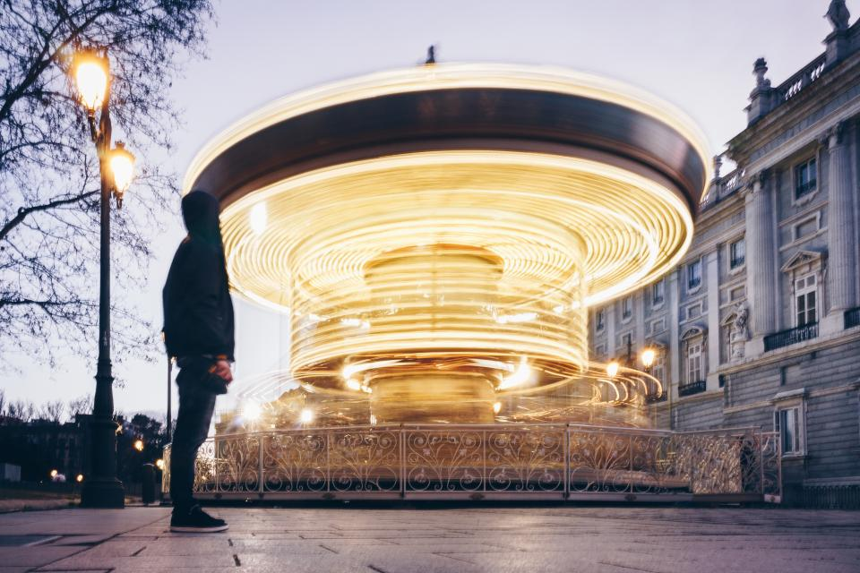 long exposure carousel ride people man amusement park lamp post trees lights building establishment