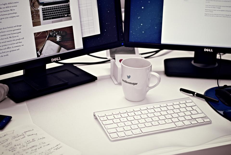 desktop computer keyboard dual monitors screens mouse peripherals coffee cup mug desk working office business pen