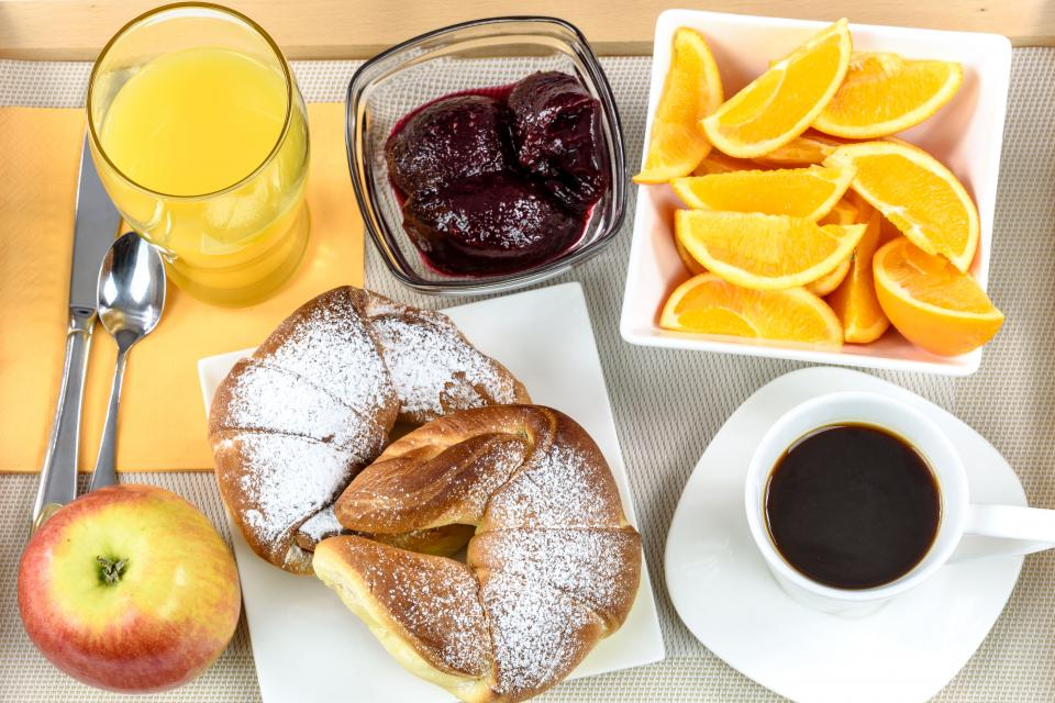 orange citrus apple fruits food bread black coffee strawberry jam juice table breakfast cutlery restaurant