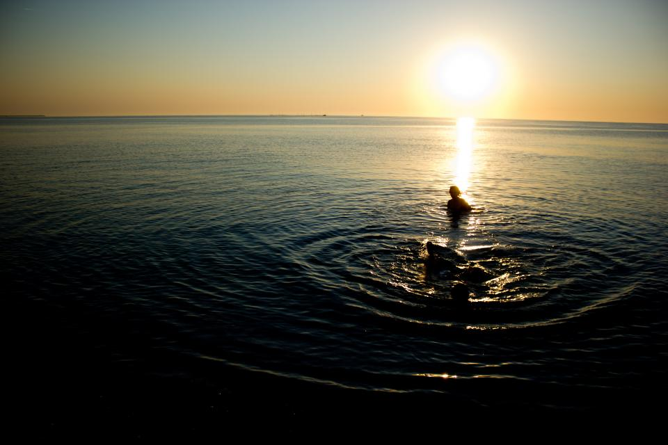 sea ocean water sunset sunrise people swimming horizon reflection nature