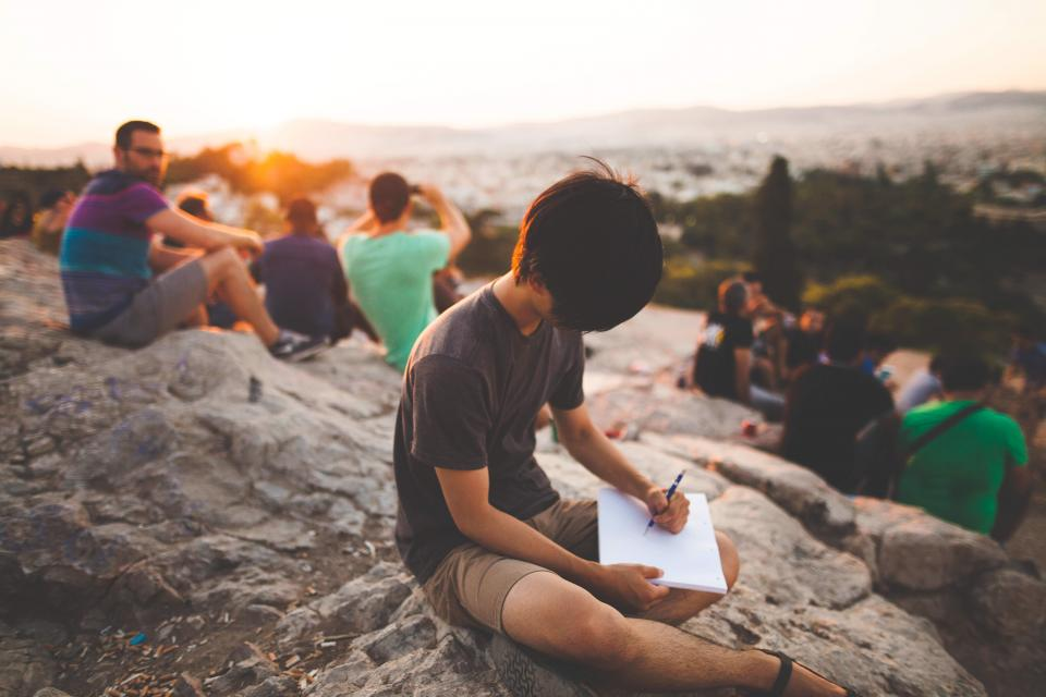 group friends people writing pen pencil paper notepad notebook sunset rocks outdoors nature adventure