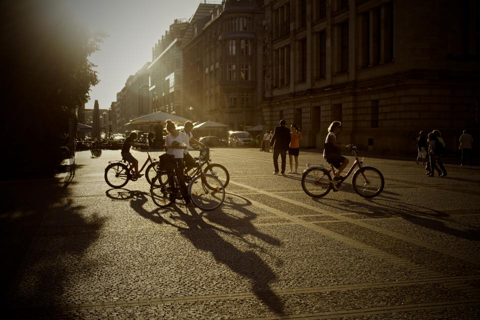 bikes bicycles people pedestrians summer streets road pavement sunset shadows buildings city