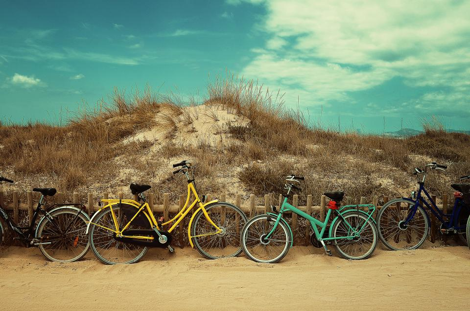 transportation bicycles wheels transportation hobby cycling mountain dirt road soil hills grass sky clouds queue