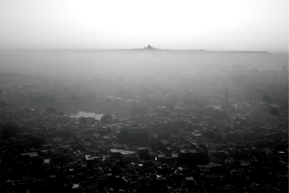 city aerial view buildings rooftops architecture fog sky black and white