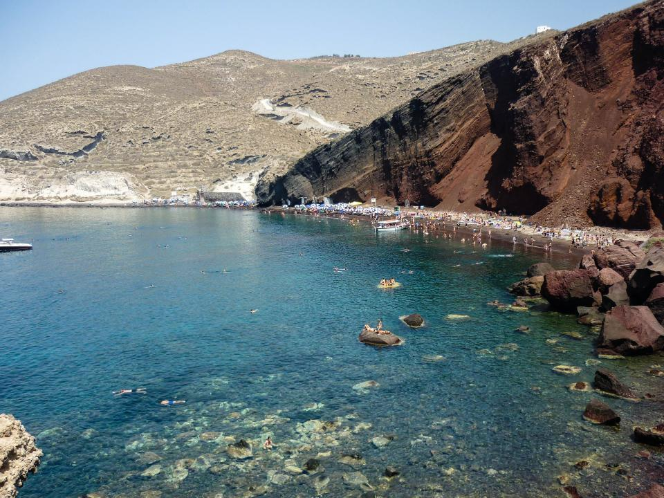 Red Beach Santorini Greece water sand people swimming boats rocks hills cliffs crowd