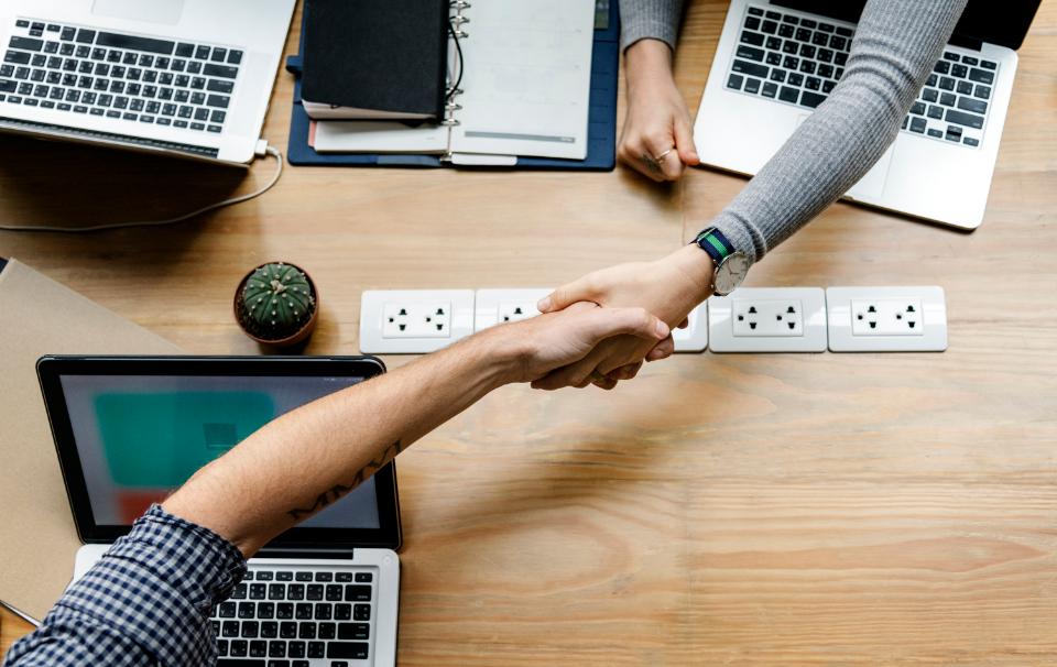 achievement agreement arms business agreement business deal caucasian collaboration colleague communication computer connection cooperation deal european friends grasp greeting hands handshake helping hands investment laptop meeting