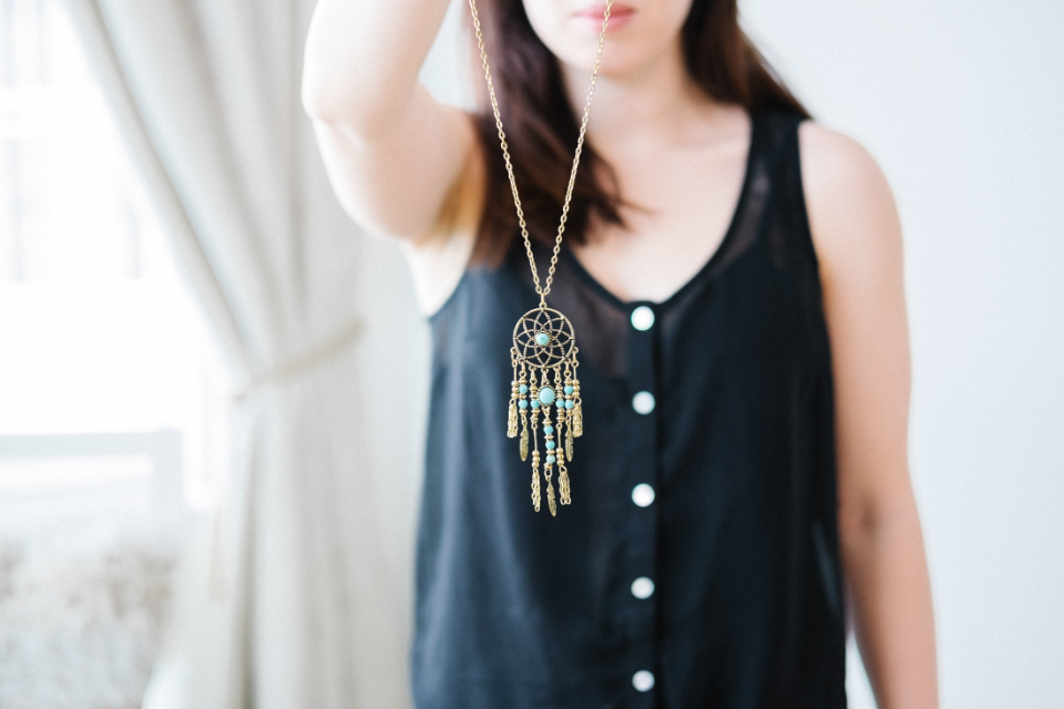 woman close up person pose necklace female lips fashion neck jewelry hair holding dreamcatcher charm