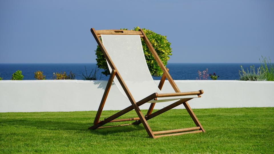 still items things foldable chair lawn manicured grass wall plants bushes water sky horizon leisure