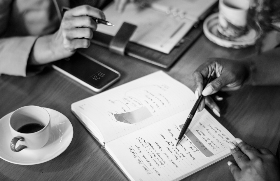 business meeting analysis brainstorm businesswoman cafe close up coffee communication corporate correspondence cup notebook notes phone discussion drink financial report focus grayscale monochrome hands ideas lunch marketing mobile phone notepad note