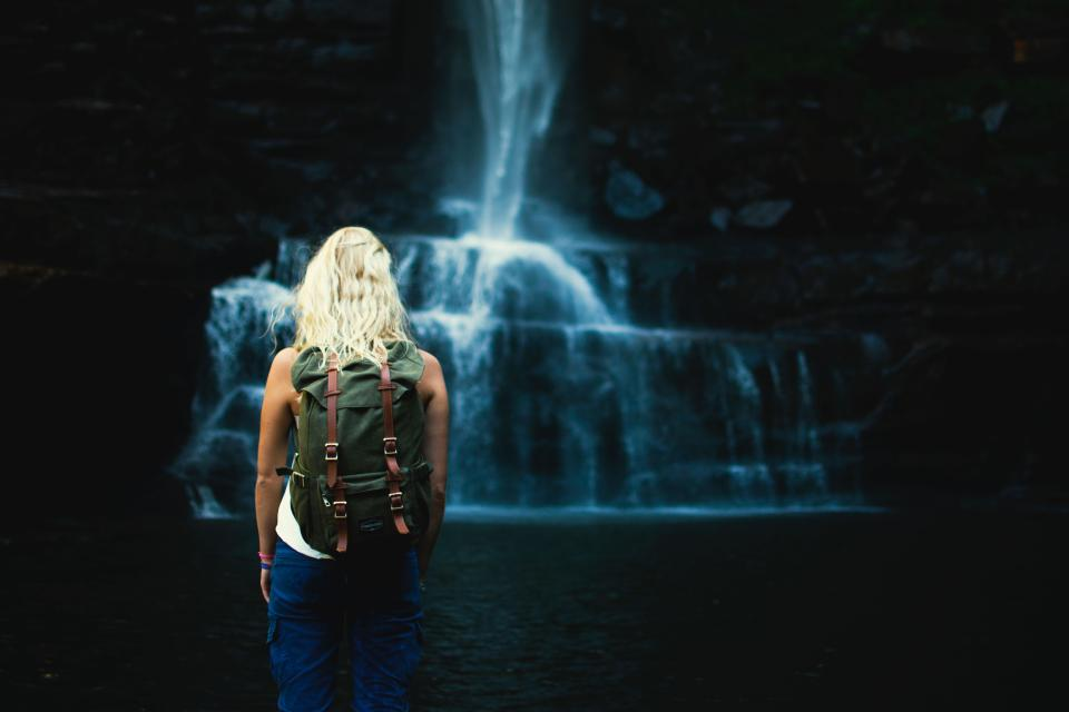 waterfalls stream water dark cave people woman girl alone travel adventure outdoor backpack