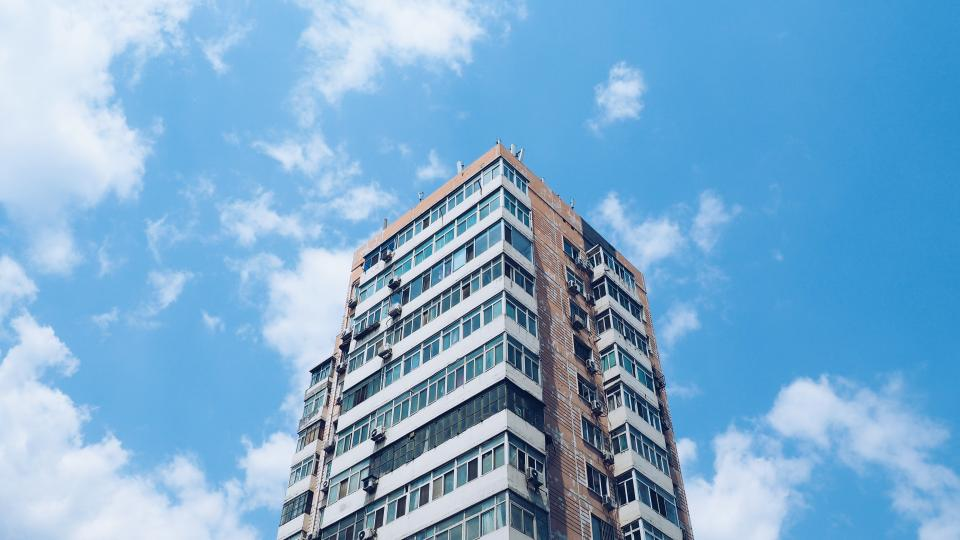 apartment condo building architecture blue sky clouds city urban
