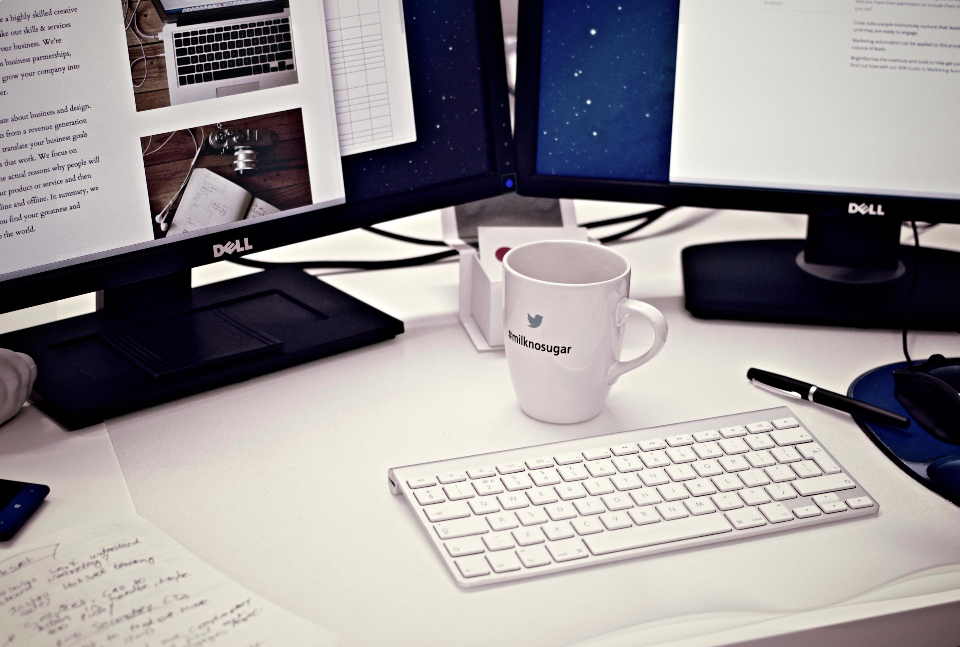 white desk office monitor computer coffee mug mac keyboard minimal dual pen notes