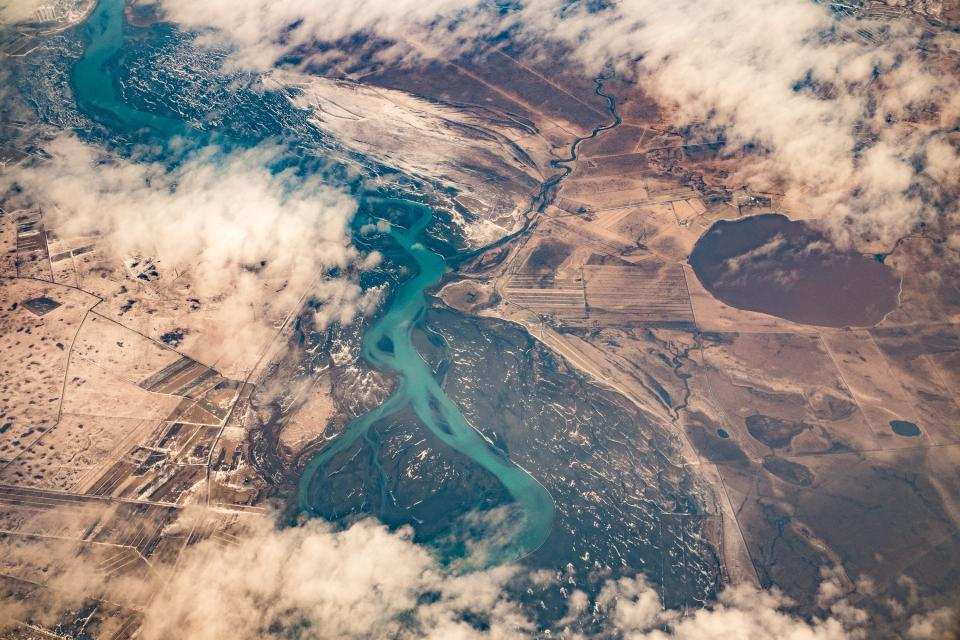 aerial view sky clouds airplane travel flying above the clouds fields landscape river water