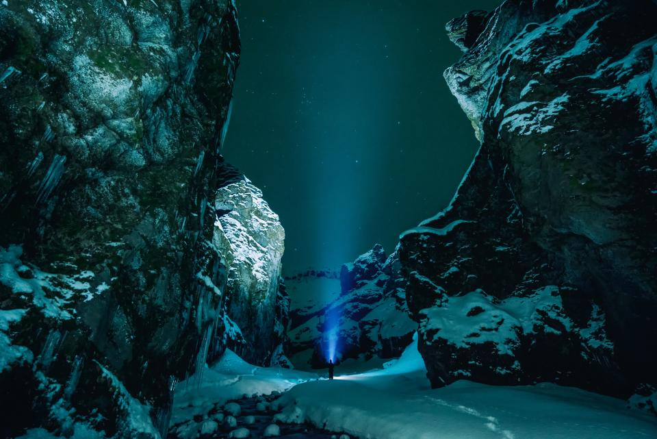 ice cave rocks snow winter flashlights people travel outdoor adventure hill
