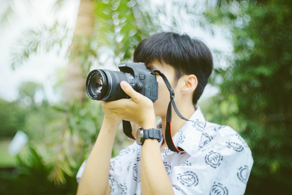 camera lens accessory photography photographer people guy blur bokeh trees green plants outdoor
