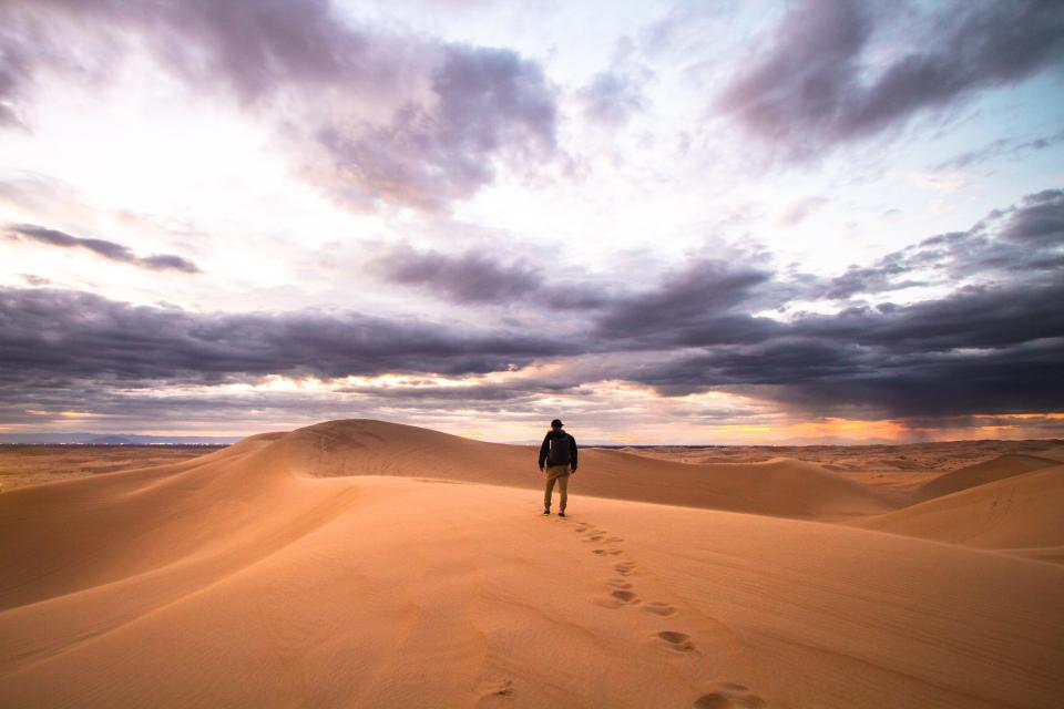 people man alone travel adventure sand desert clouds sky footsteps nature