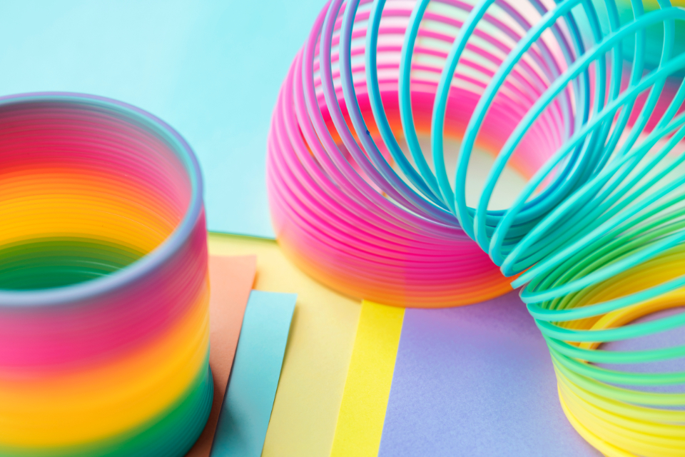 abstract background bright childhood closeup coil colored colorful enjoyment entertainment equipment flexibility flexible fun funky game kids leisure macro memories metal motion object pattern plastic play rainbow recre