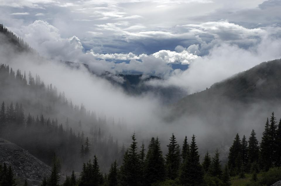 sky clouds mountains hills trees nature outdoors woods fog haze hike trek