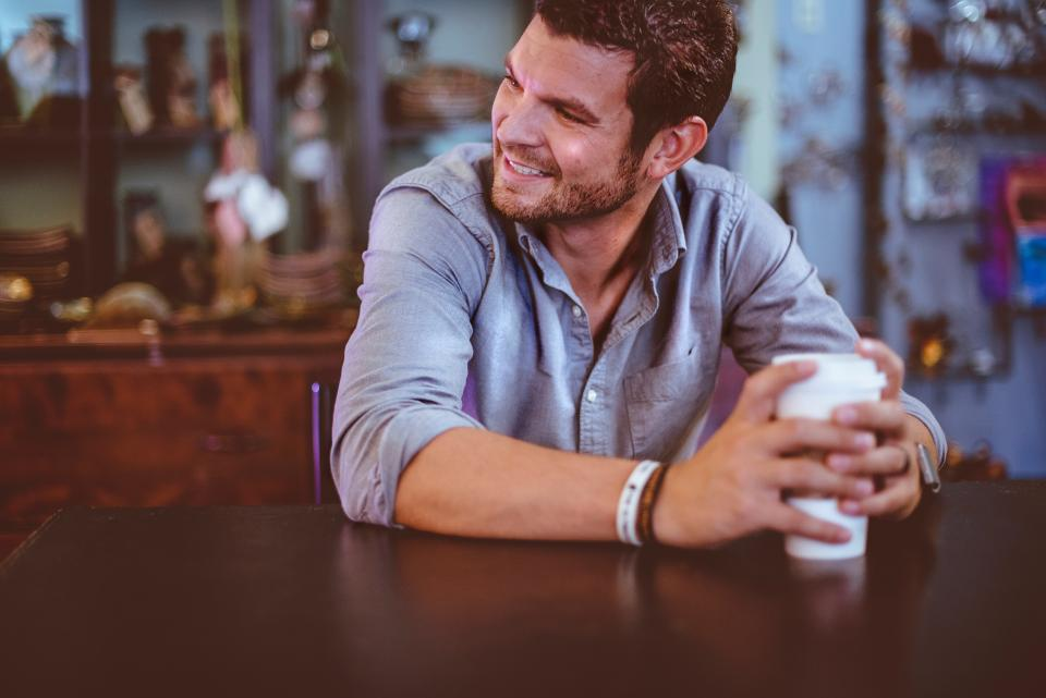 people man coffee cup sitting smile happy coffeeshop table