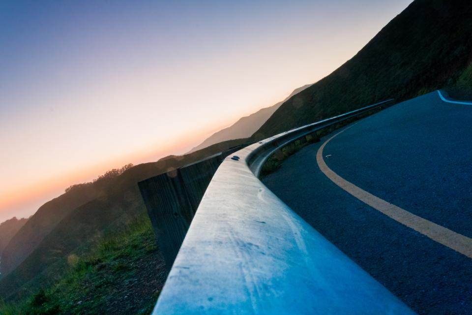 winding road corner railing mountains sky sunset dusk guard rail
