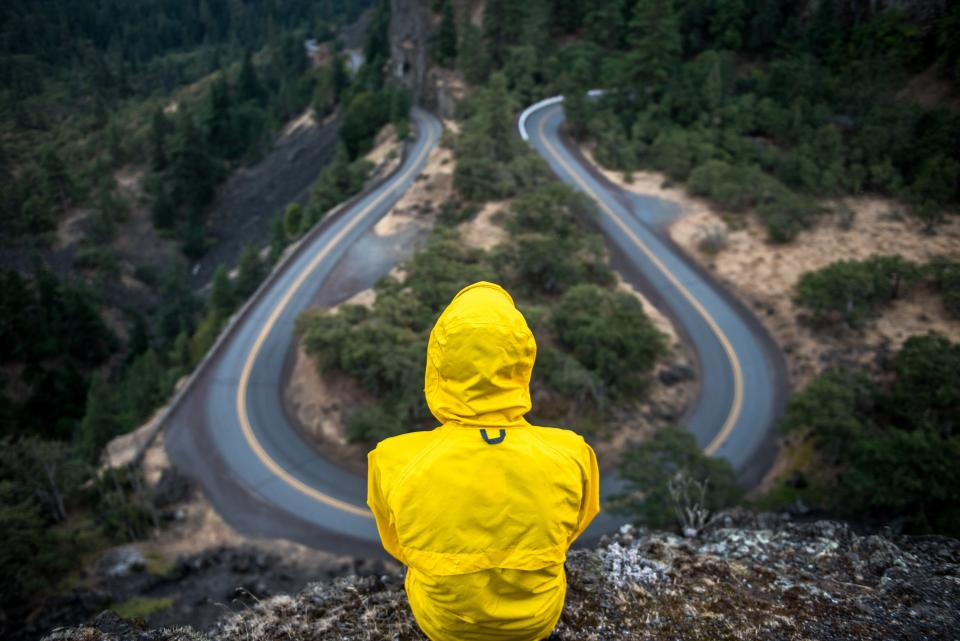yellow jacket rain coat people rural winding road hairpin countryside cliff nature trees