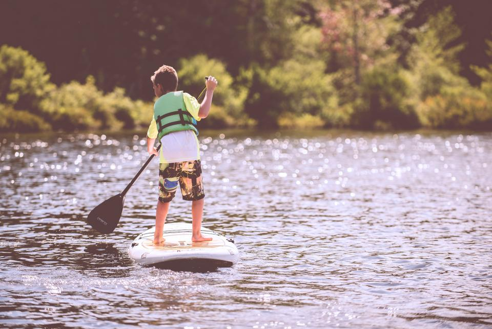 people kid child boy sailing paddle board lake water sunshine nature trees adventure outdoor vacation sport