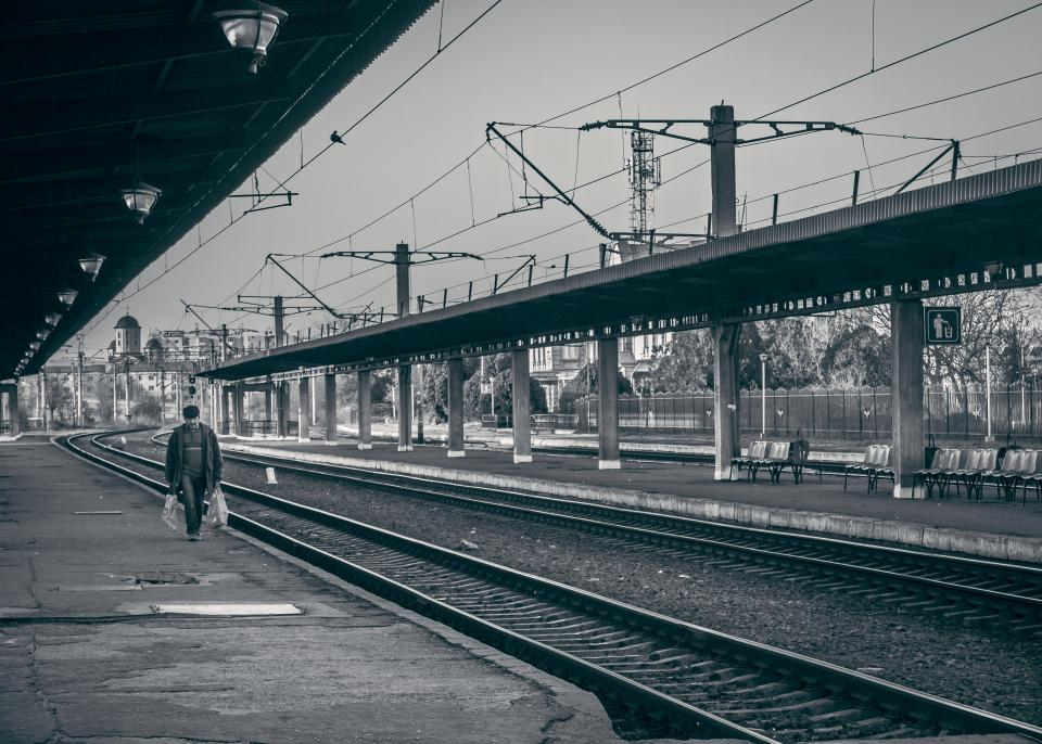 railway railroad train tracks transportation people walking pedestrian train station city urban black and white