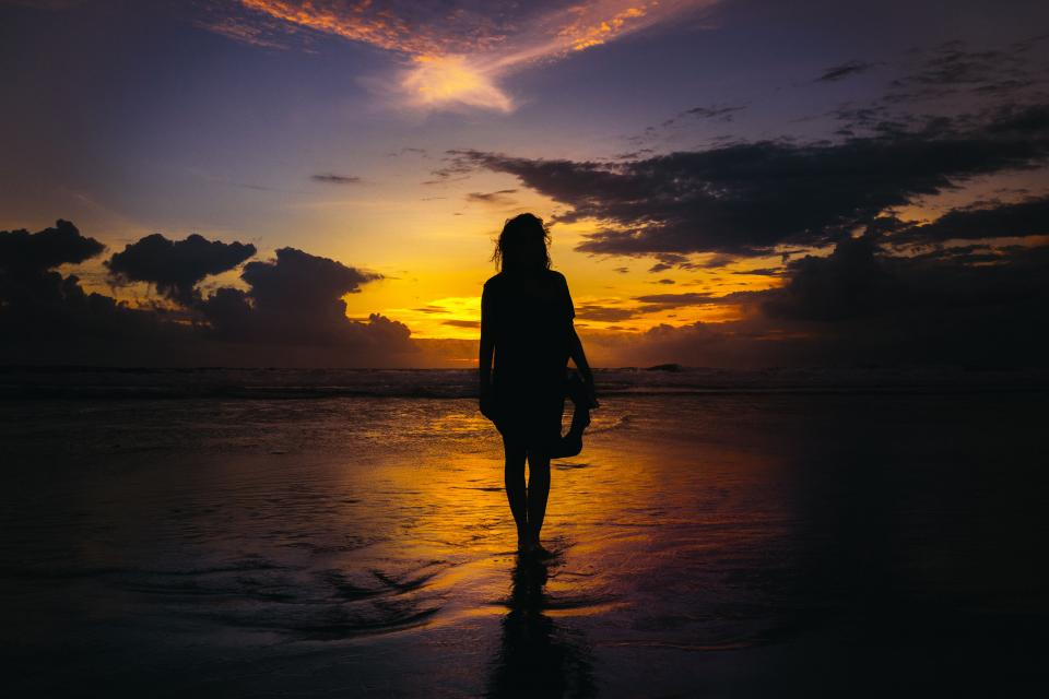 people girl woman walking alone sunset sea water beach shore coast silhouette cloud sky