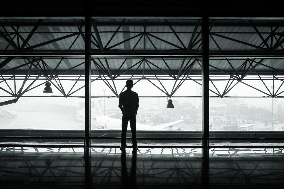 airport airplanes hanger terminal window beams lights man shadow black and white