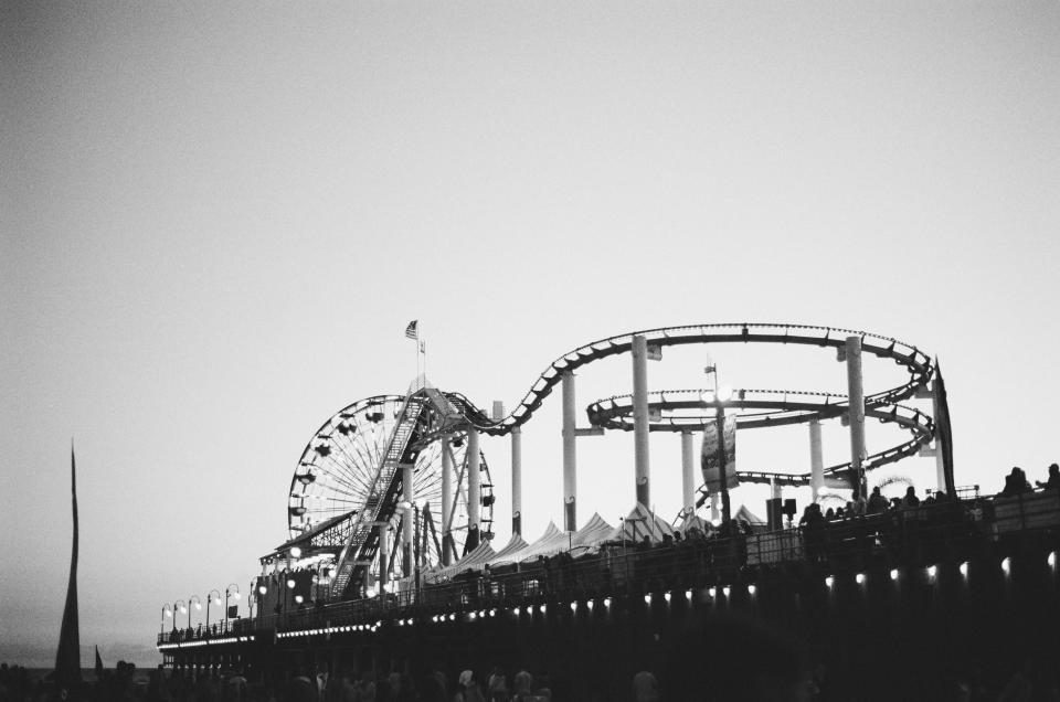 amusement park carnival rides roller coaster ferris wheel tents pier people crowd black and white flag usa fun