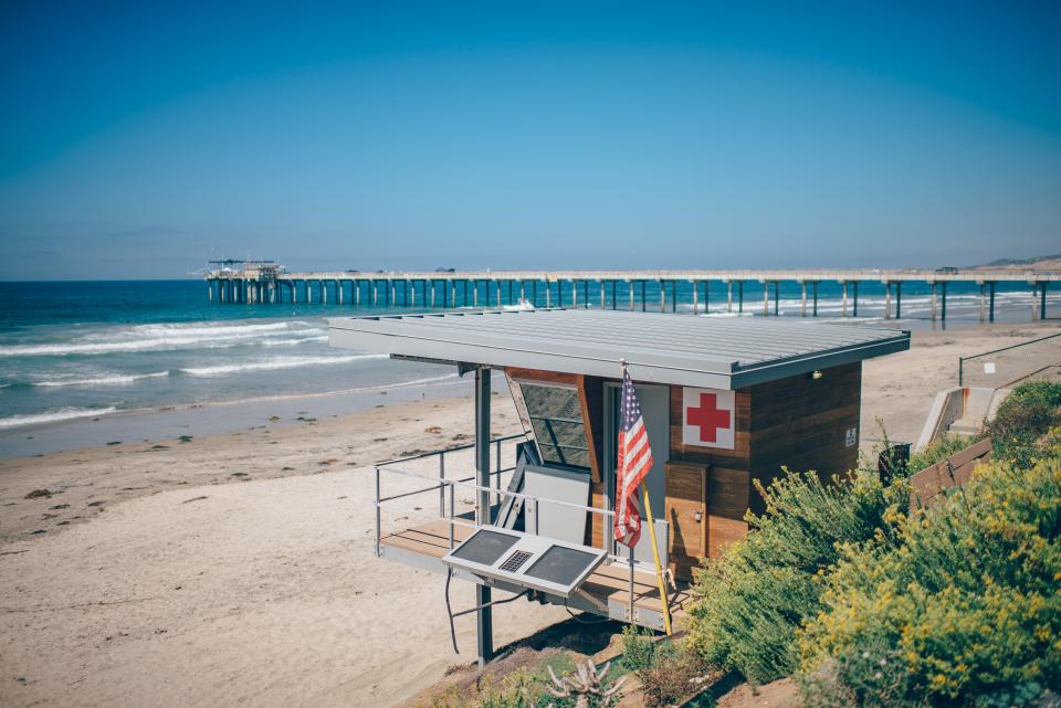 beach sand lifeguard hut american flag USA summer blue sky sunshine shore ocean sea waves pier outdoors