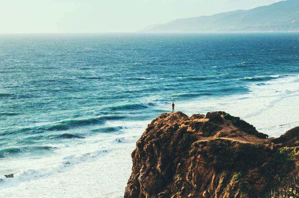 people man guy back alone sea beach water wave coast rock formation nature sky clouds fog mountain