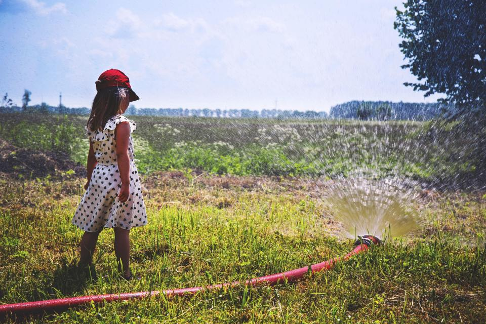 girl child people back play water hose sprinkler splash style fashion grass trees sky clouds horizon