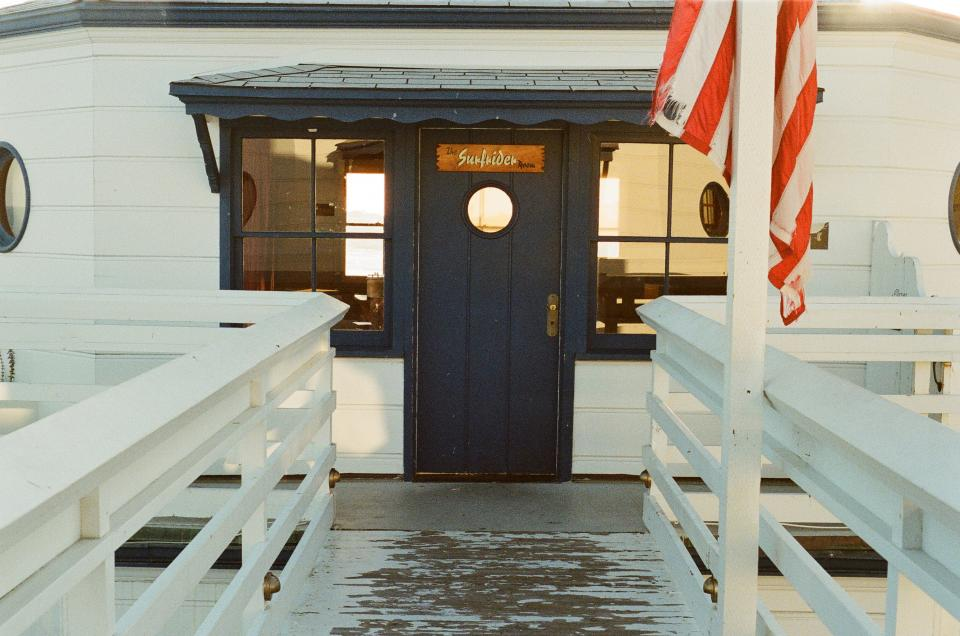 malibu surfrider wood pier railing flag entrance door window roof white
