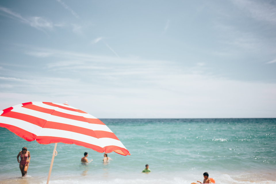 beach people umbrella ocean water horizon sky clouds outdoors swimming relax leisure swimming suit sunny summer warm