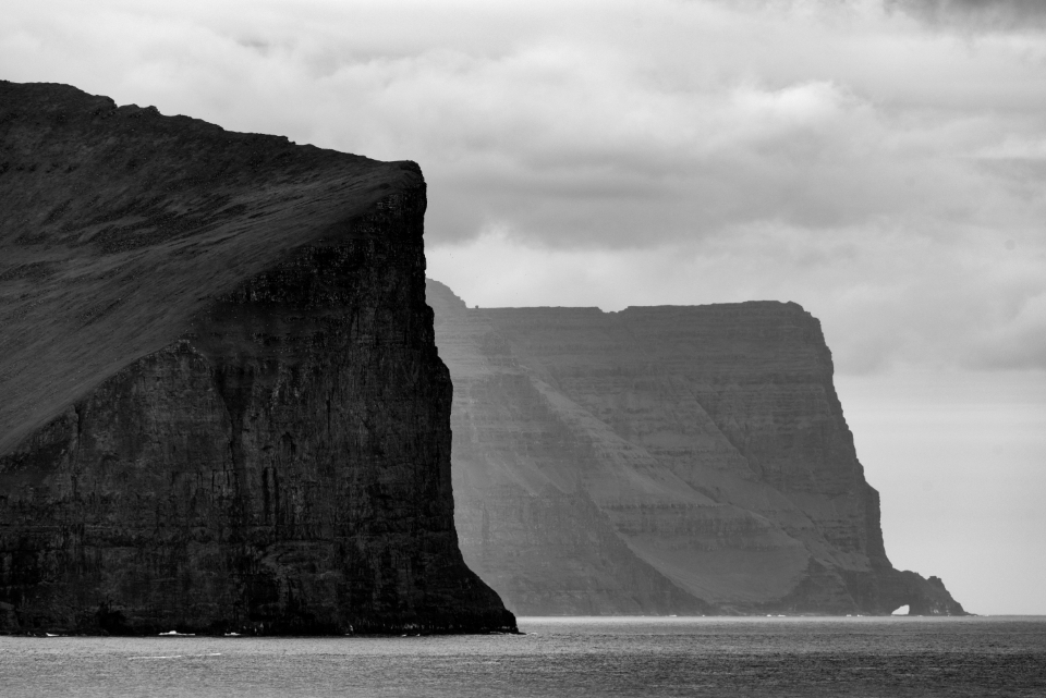 tall ocean cliffs water outdoors nature sky clouds mountains black and white moody gloomy dramatic coast rocks landscape