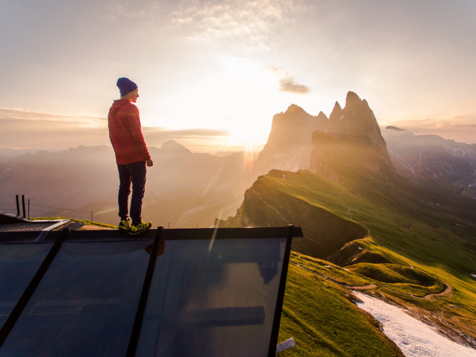 hiker sunset mountains view scenic sky clouds sunlight nature outdoors landscape altitude elevation man person standing