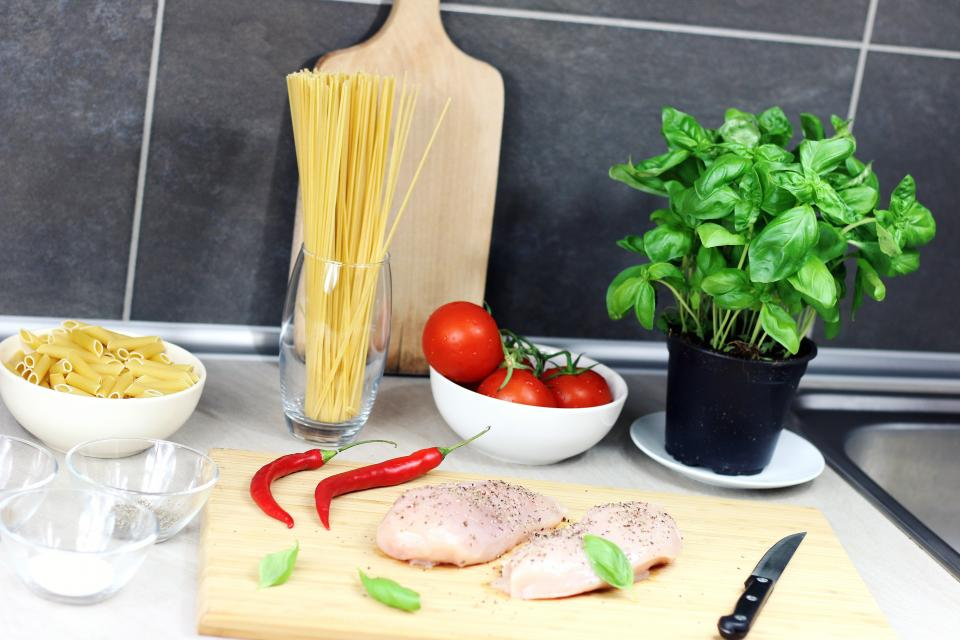 cooking food kitchen ingredients chicken meat peppers pasta spaghetti tomatoes cutting board knife bowls plant counter