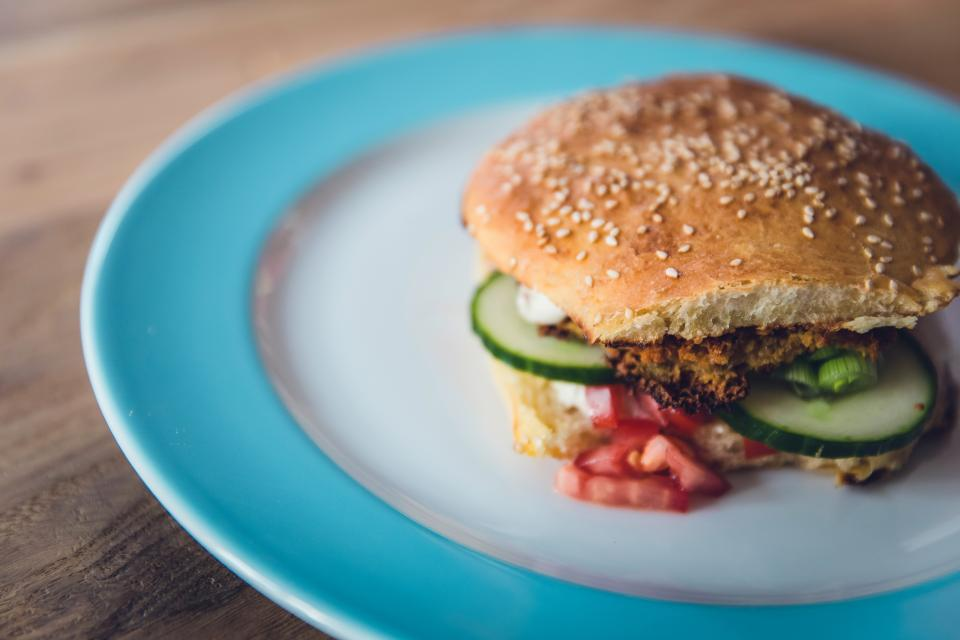 food burger plate wooden table cucumber egg beef tomatoes sesame seeds snack breakfast hamburger meal bread