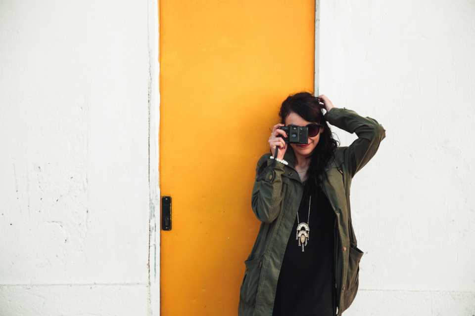 photographer woman smile fashion hip picture taking yellow door fun artist camera lense journalist portrait person
