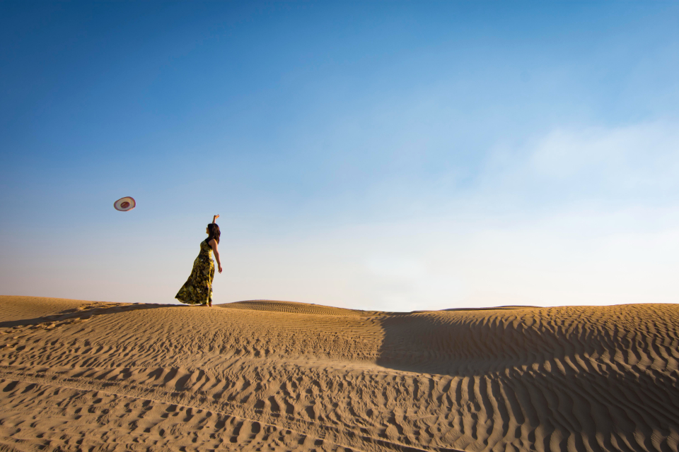woman throwing hat sand dune desert blue sky girl female clouds hot dress summer fashion model
