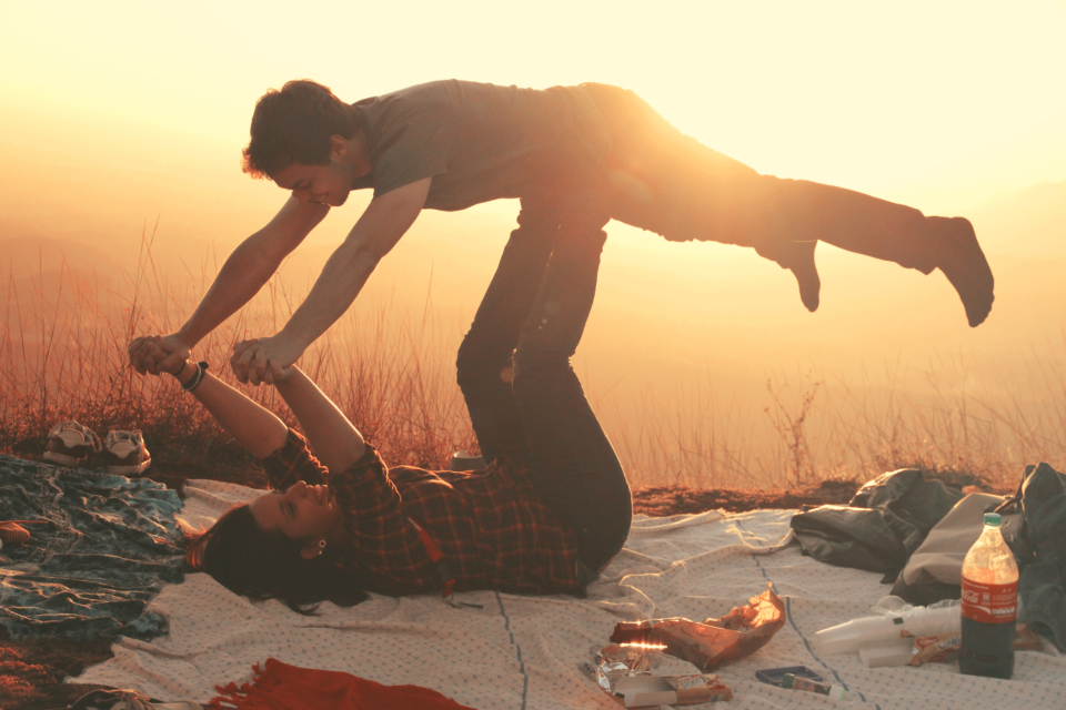 woman lifting man blanket picnic happy sunset sun drink food romantic love couple female male