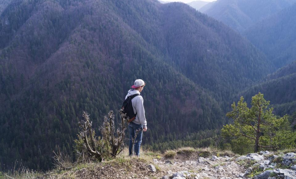 guy man male people side view contemplate style backpack nature mountains travel trek hike climb summit peaks fog vegetation grass trees rocks